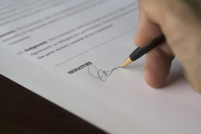 Dieses Bild zeigt wie ein Dokument unterschrieben wird